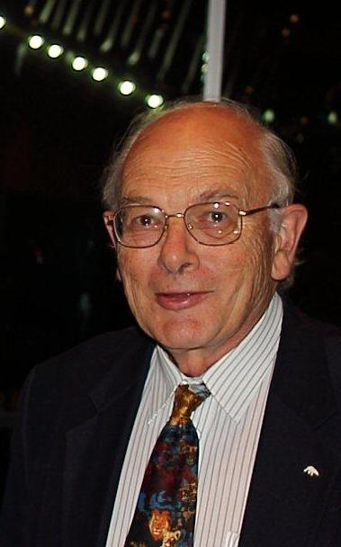 Head and shoulders photograph of an elderly, balding, white man wearing glasses and dressed in a suit.